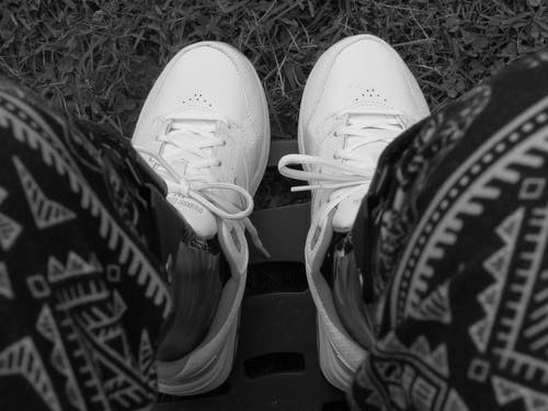 Grayscale Photo of White Sneakers