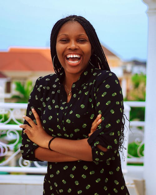 Happy African American female with African braids in trendy dress laughing and standing with arms crossed on terrace in daytime