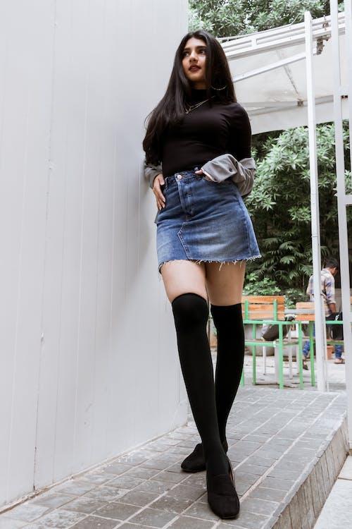 Woman in Black Long Sleeve Shirt and Blue Denim Skirt Standing Beside White Wall