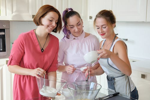 Joyful females mixing ingredients in bowls for baking cakes while cooking together in modern light kitchen