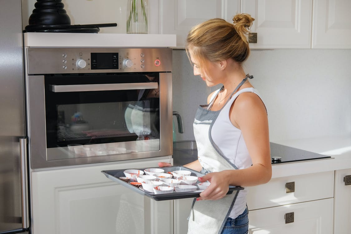 Glad woman with baking pan standing near oven
