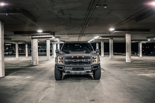 Modern gray pickup with glowing headlights parked on asphalt in underground parking lot with columns in evening time in city