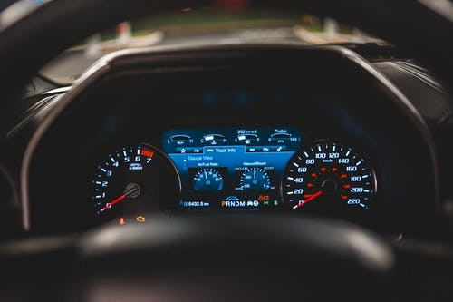 View of glowing instrument panel through steering wheel of contemporary automobile with black interior and blurred street through windshield outside