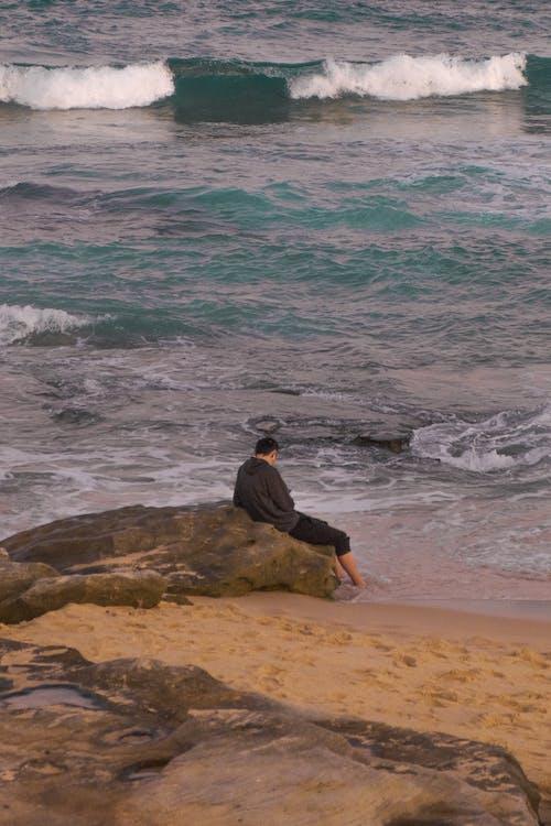 Man Sitting on Brown Rock Near Body of Water