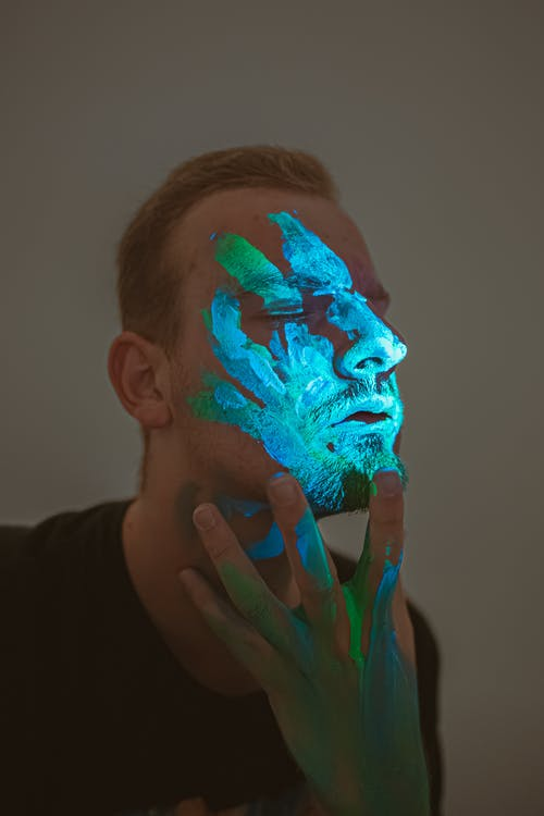 Calm man with neon paint on face touching chin