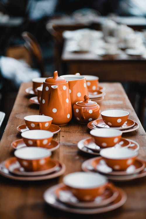 Orange and White Ceramic Tea Cups on Brown Wooden Table