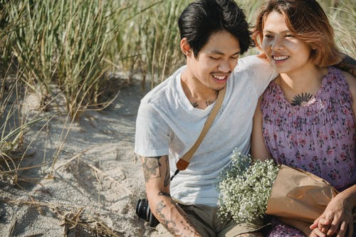 Man in White Crew Neck T-shirt Sitting Beside Woman in Purple Floral Dress
