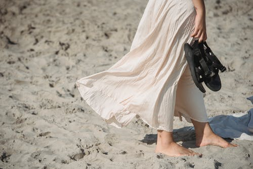 Woman in White Dress Walking on Sand