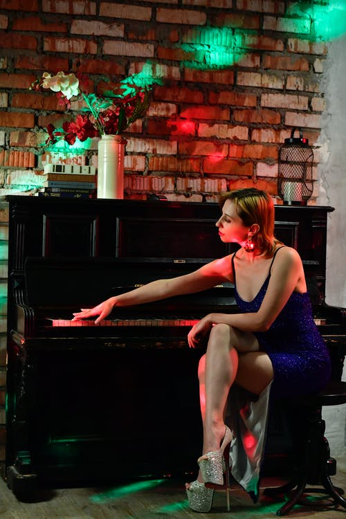 Full body side view of stylish female musician in dress and high heels touching keyboard of piano while sitting on chair crossed legged