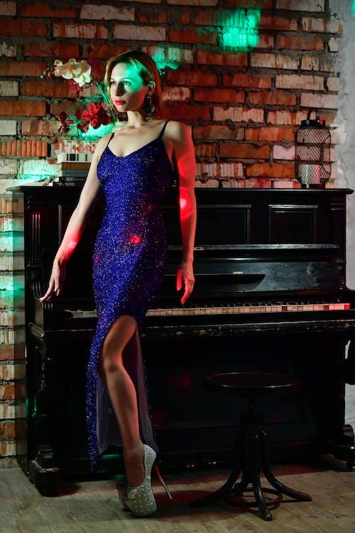 Elegant woman standing near piano
