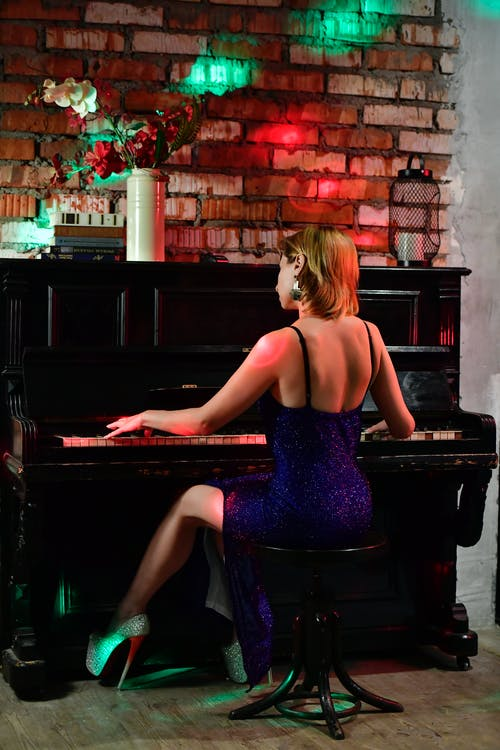 Back view full body of anonymous female musician in elegant dress playing piano while rehearsing in room with flowers in vase and bright lights