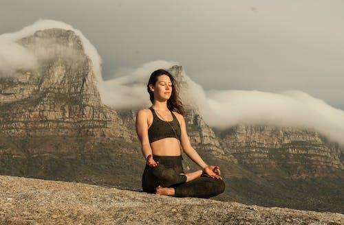 滝の近くの岩の上に座っている黒いブラジャーと黒いズボンの女性