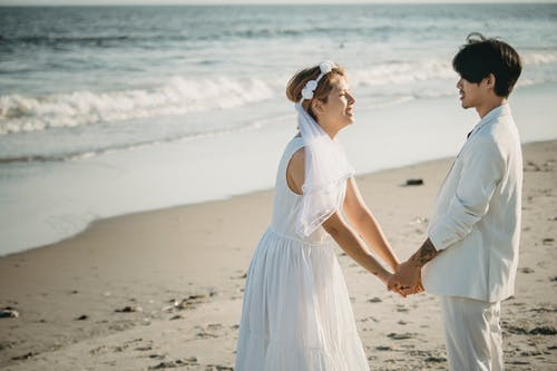 Woman in White Dress Holding Hands With Man in White Suit at Beach