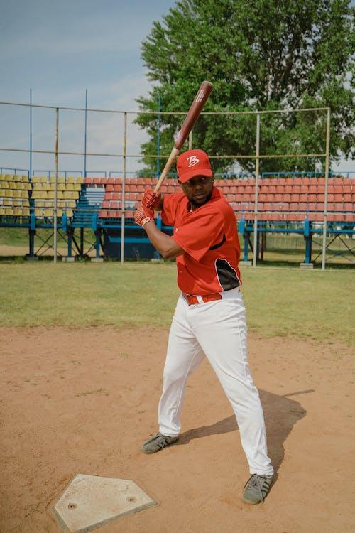 Man in Red Baseball Jersey Holding a Baseball Bat