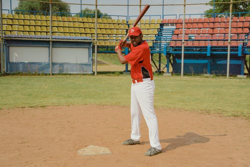 Man in Red Shirt and White Pants Holding Baseball Bat