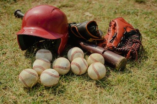 Red Baseball Helmet on Green Grass Field