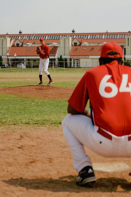 Man in Red Jersey Shirt and White Pants Standing on Baseball Field