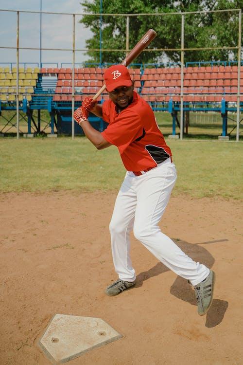 Man in Red Baseball Cap Swinging a Baseball Bat