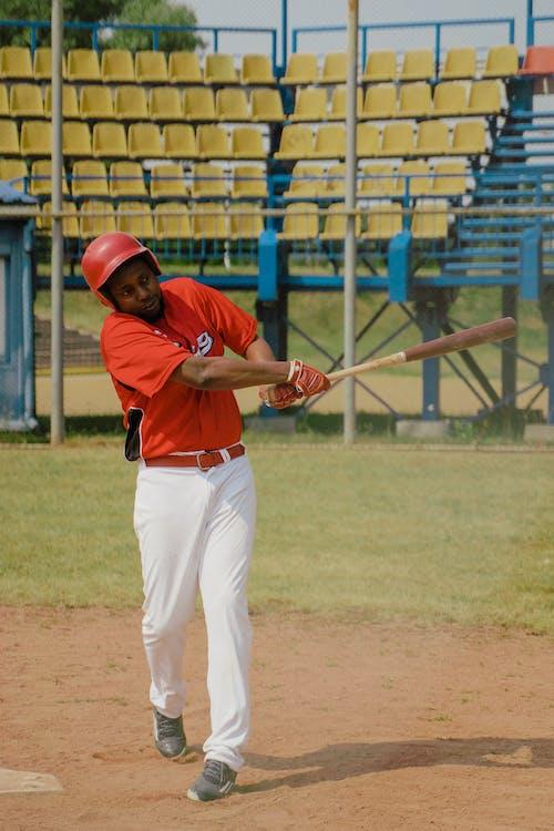 Man in Red Baseball Jersey Swinging a Baseball Bat