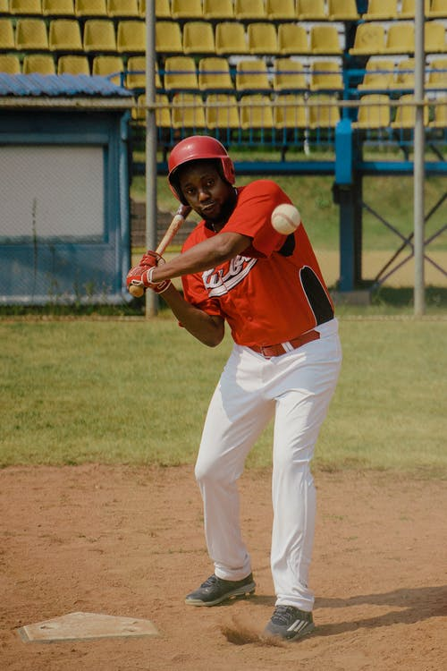 Man in Red Jersey Shirt and White Pants Holding Baseball Bat