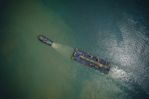 High angle of modern vessel with cargo trailer floating on rippling water of sea in sunny day