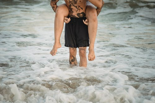 Man in Black Shorts Carrying Woman on his Back