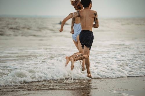 Man in Black Shorts Running on Beach