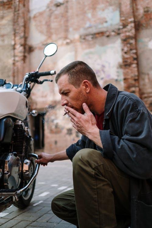 Man in Black Jacket Smoking While Sitting Near Motorcycle