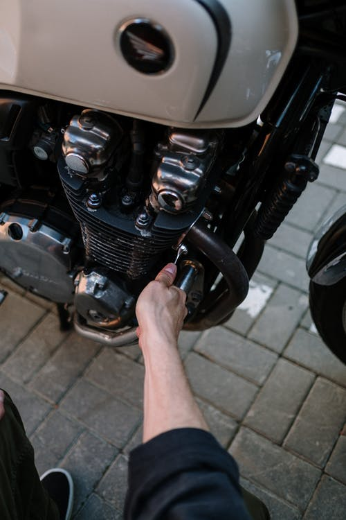 Person Fixing Black Motorcycle
