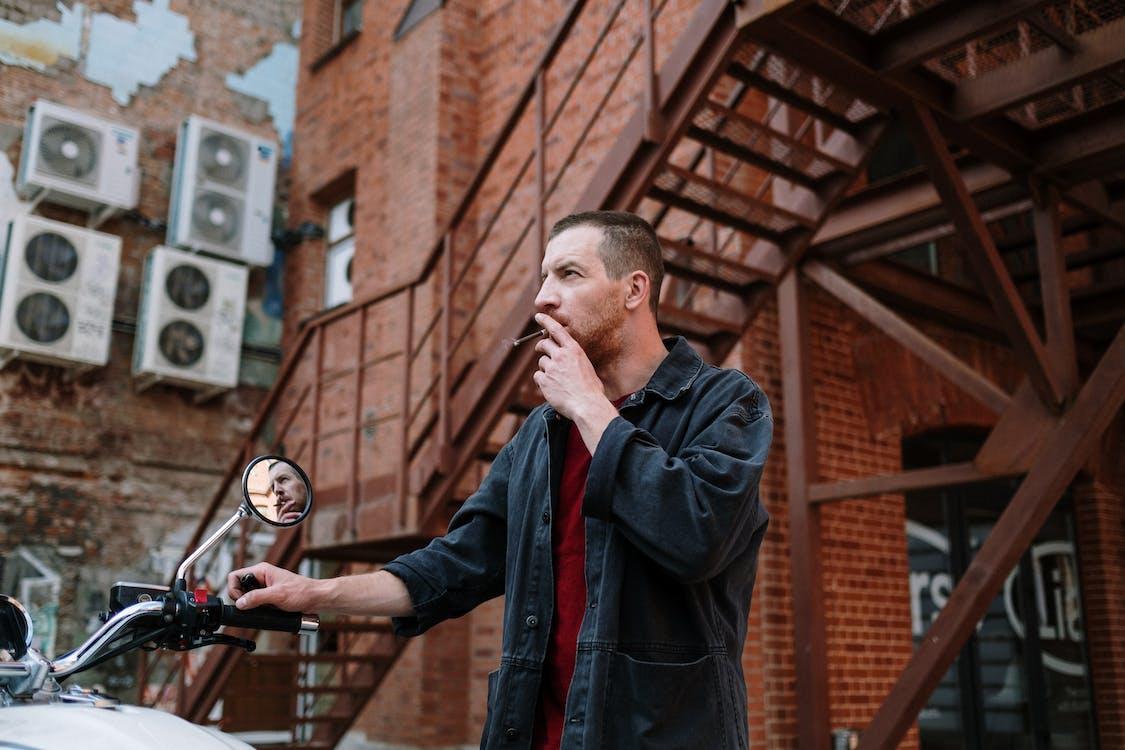 https://www.pexels.com/photo/man-in-black-jacket-smoking-beside-motorcycle-in-front-of-brick-building-5184994/