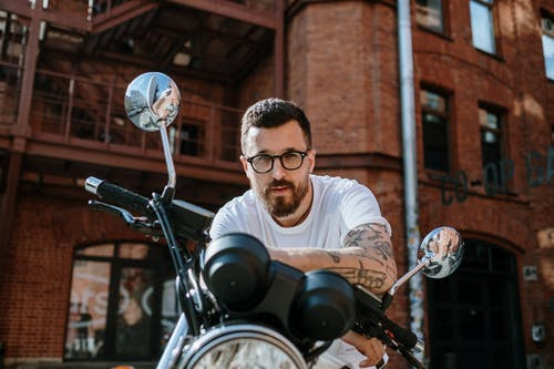 Man in White Crew Neck Shirt Riding on Black Motorcycle