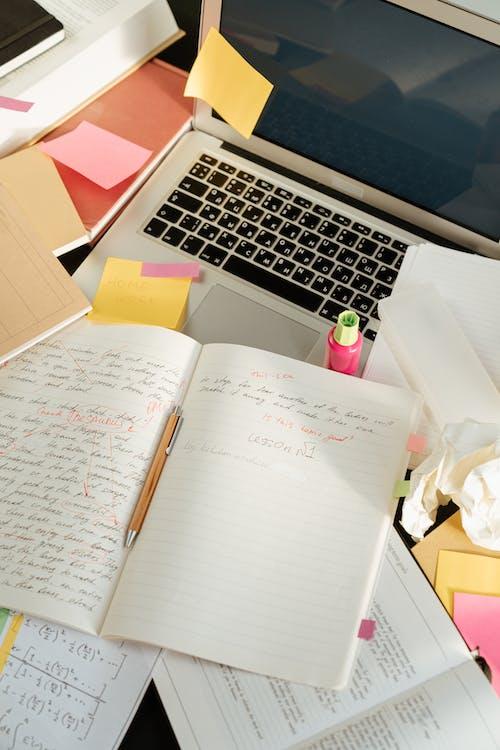 Macbook Pro Beside White Printer Paper