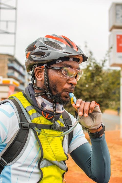 Man in Yellow and Black Vest Wearing Helmet