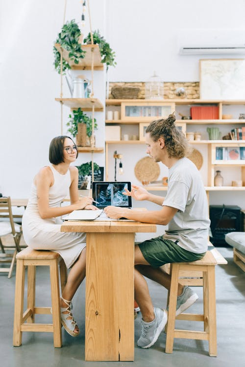 Man and Woman Sitting on Chair Working Together