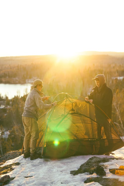 Young men setting up tent on campsite at sunset