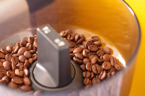 Brown Coffee Beans on Stainless Steel Cup