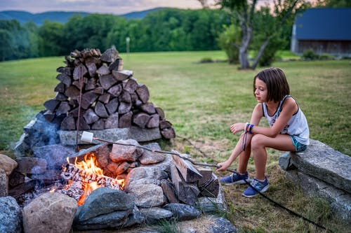 Full body of little girl in summer outfit sitting on stone bench and roasting marshmallow on twig on fire near boulders and logs on grassy field near trees in summer evening