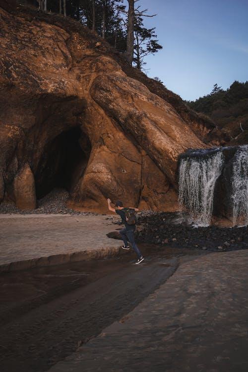 Unrecognizable hiker walking in mountainous terrain near waterfall