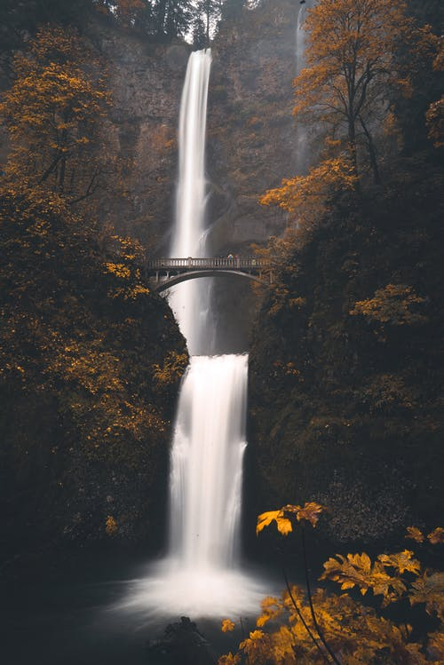 Bridge over waterfall streaming in autumn forest