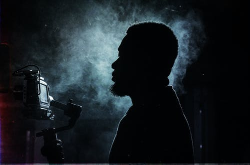 Side view silhouette of serious bearded male videographer recording video on professional video camera while standing in dark smoky studio