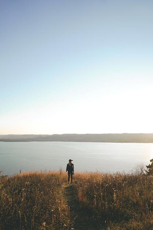 Unrecognizable tourist recreating on lake shore