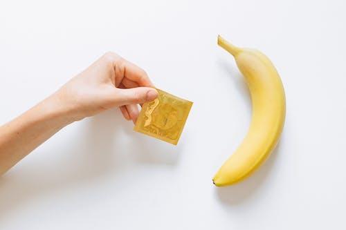 Person Holding Condom Next to Banana