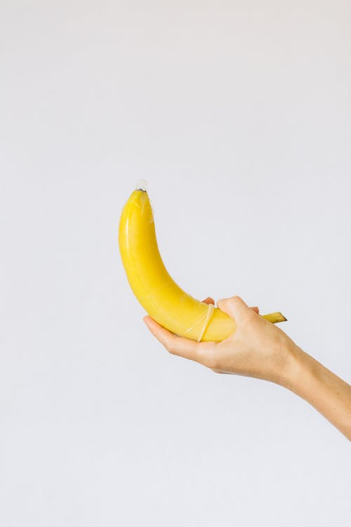 Person Holding Banana Wrapped in Condom