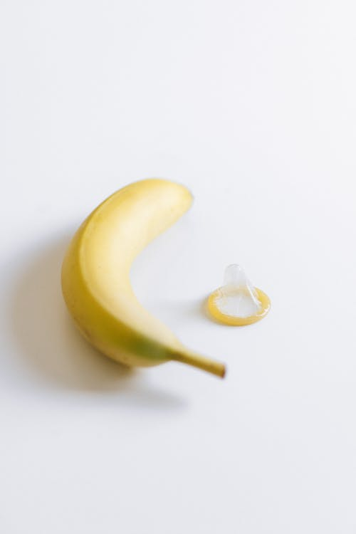 Unwrapped Condom Next to Banana