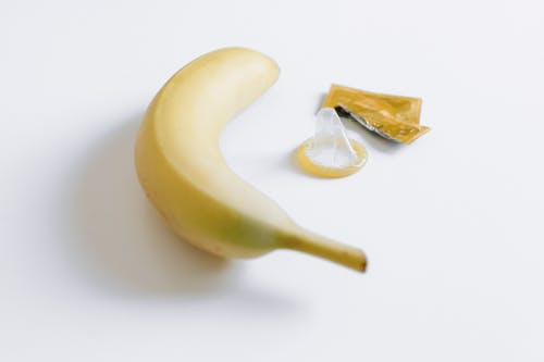 Unwrapped Condom Next to Banana
