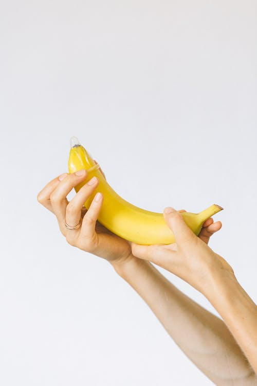 Person Wrapping Condom on Banana