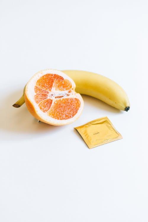 Condom Next to Banana and Orange Fruit