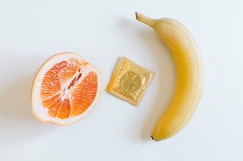 Condom Between Orange and Banana