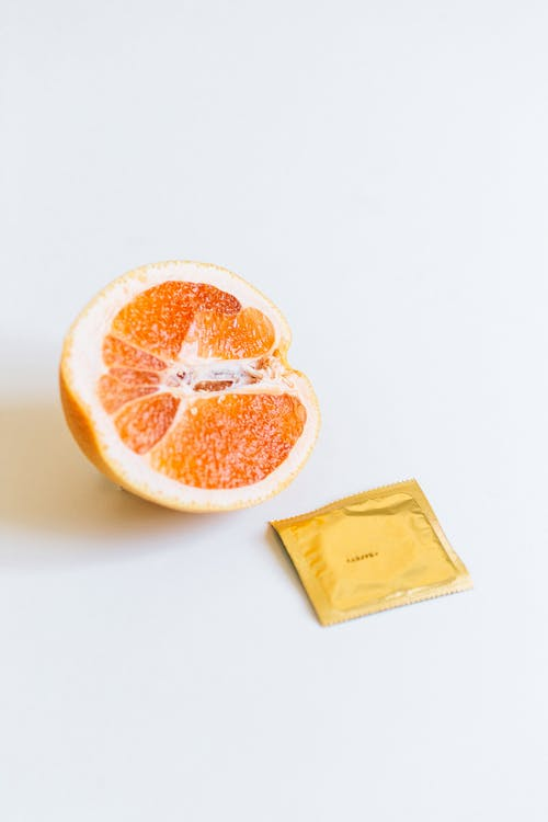 Condom Next to Orange Fruit
