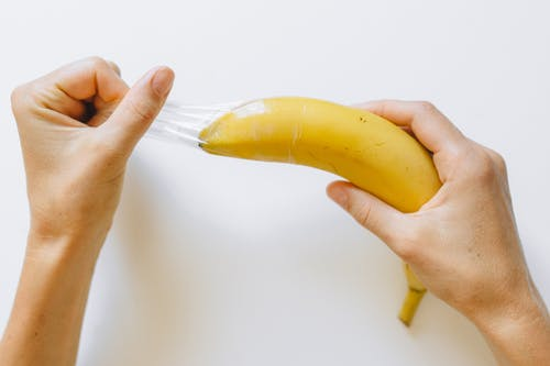 Person Pulling Condom Off Banana